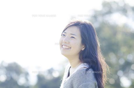 木をバックに笑顔の女性の素材 [FYI01077063]