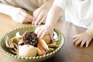 机の上にあるポプリを触る男の子と母親の手の素材 [FYI01077068]