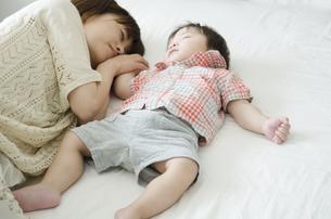 シーツの上で眠る男の子とお母さんの素材 [FYI01077079]