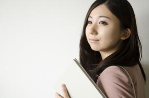 バッグを肩に掛けて本を持つ女性の素材 [FYI01077081]
