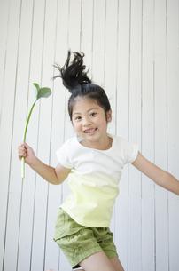 葉っぱを持ってジャンプをする女の子の素材 [FYI01077082]