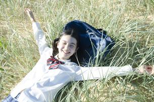 制服姿で草原に寝転がって手を広げる女の子の素材 [FYI01077084]