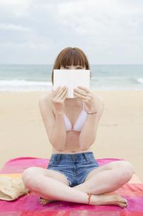 ビーチに座って本で顔を隠すビキニ姿の女性の素材 [FYI01077091]