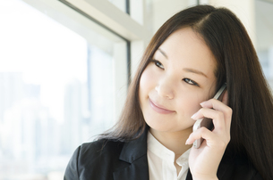 窓際で電話をするスーツ姿の女性の素材 [FYI01077094]