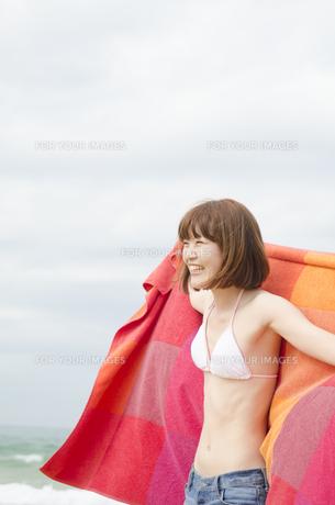 ビーチでタオルを広げて笑うビキニ姿の女性の素材 [FYI01077095]