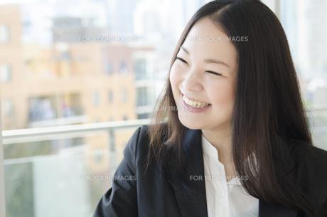 窓際で笑うスーツ姿の女性の素材 [FYI01077097]
