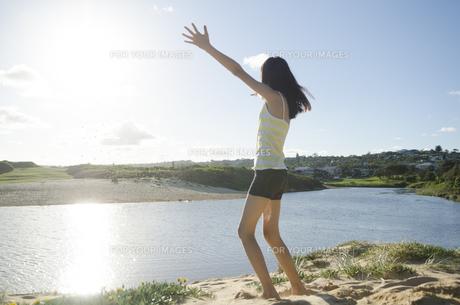 ビーチで砂を放り投げる女の子の素材 [FYI01077105]