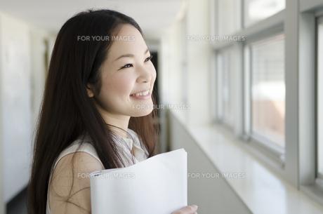 書類を抱えて廊下で笑うOLの素材 [FYI01077106]