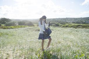 制服姿でヘッドフォンを着けて草原を歩く女の子の素材 [FYI01077111]