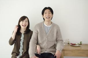 室内で並んで大笑いするカップルの素材 [FYI01077118]