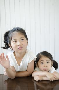白い服を着て机に腕を乗せる姉妹の素材 [FYI01077119]