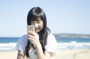 ビーチで笑顔で携帯電話をいじっている制服姿の女の子の素材 [FYI01077124]