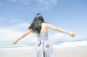 ビーチで手を広げる黒髪の女性の素材 [FYI01077127]