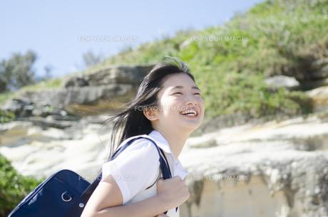 カバンを肩に掛けて笑う制服姿の女の子の素材 [FYI01077136]