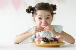 カップケーキを食べるハーフの女の子の素材 [FYI01077137]