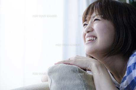 ソファに手を置いて笑う女性の素材 [FYI01077142]