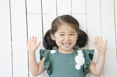 壁の前でポーズを取る笑顔の女の子の素材 [FYI01077143]
