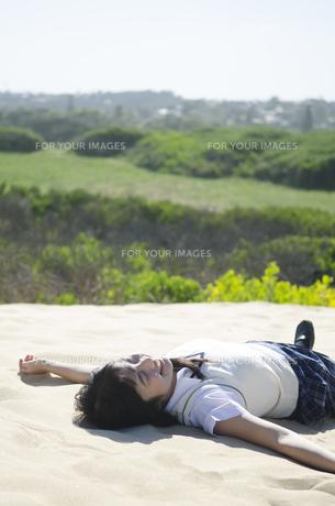 砂浜に仰向けに寝そべる制服姿の女の子の素材 [FYI01077147]