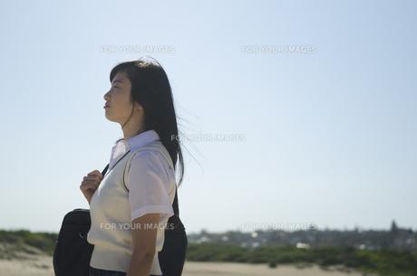 カバンを肩に掛けて遠くを見る制服姿の女の子の素材 [FYI01077148]