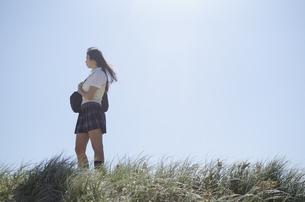 草むらにたたずむ制服姿の女の子の素材 [FYI01077150]