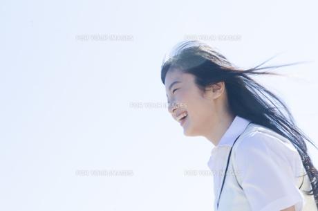 髪をなびかせて笑う制服姿の女の子の素材 [FYI01077155]
