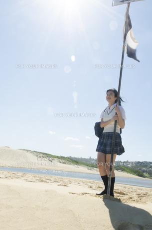 旗に手を掛けてビーチに立つ制服姿の女の子の素材 [FYI01077159]
