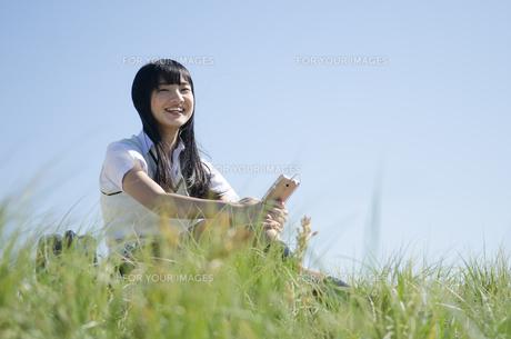草むらに座って笑顔で音楽を聞いている制服姿の女の子の素材 [FYI01077163]