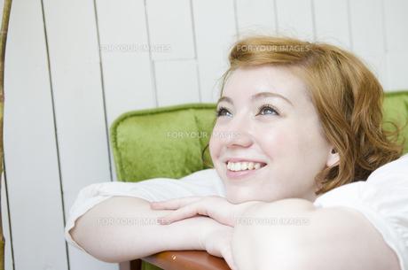 緑のソファに手を掛けて笑うハーフの女性の素材 [FYI01077164]