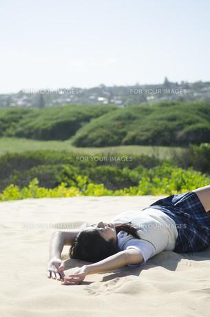 砂浜に仰向けに寝そべる制服姿の女の子の素材 [FYI01077167]