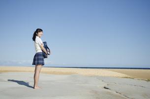 ビーチでたたずむ制服姿の女の子の素材 [FYI01077169]