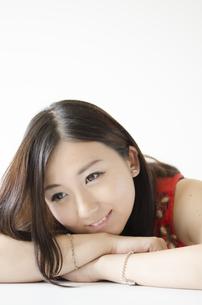 机の上に腕を組み顔を乗せて笑う女性の素材 [FYI01077173]