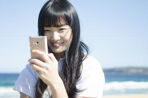 ビーチで笑顔で携帯電話をいじっている制服姿の女の子の素材 [FYI01077174]