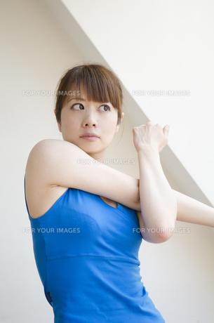 部屋の中で真剣な顔をしてストレッチをする女性の素材 [FYI01077175]