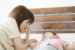 ベッドで寝かしつけるお母さんと眠る男の子の素材 [FYI01077177]