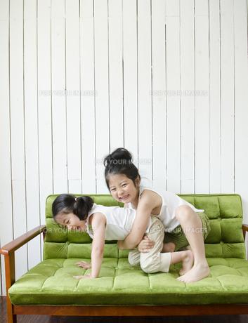 緑のソファの上で遊んでいる姉妹の素材 [FYI01077178]