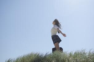 草むらに立って手を広げている制服姿の女の子の素材 [FYI01077179]