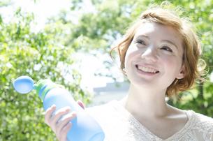 ウォーターボトルを持って笑うハーフの女性の素材 [FYI01077181]