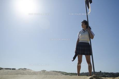 旗に手を掛けてビーチに立つ制服姿の女の子の素材 [FYI01077183]