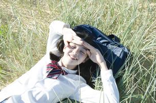 制服姿で草原に寝転がる女の子の素材 [FYI01077185]