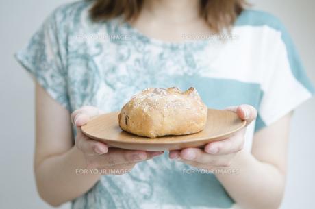 お皿に乗ったパンを持つ女性の手元の素材 [FYI01077186]