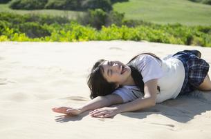 砂浜に笑いながら転がる制服姿の女の子の素材 [FYI01077188]