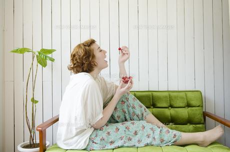 緑のソファに座ってさくらんぼを食べようとしているハーフの女性の素材 [FYI01077193]