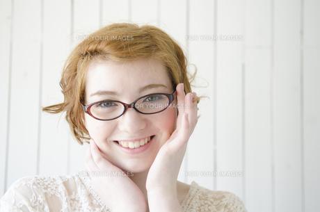 メガネのふちを持って笑うハーフの女性の素材 [FYI01077194]