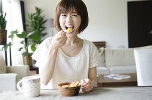 フルーツサラダを笑顔で食べる女性の素材 [FYI01077197]