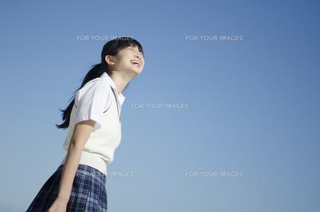 青空バックに笑う制服姿の女の子の素材 [FYI01077198]