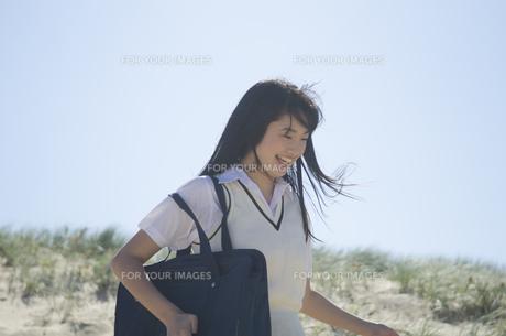 カバンを肩に掛けて笑う制服姿の女の子の素材 [FYI01077201]