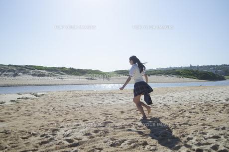 ビーチで走る制服姿の女の子の素材 [FYI01077202]