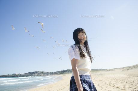 かもめをバックにビーチで笑う制服姿の女の子の素材 [FYI01077207]