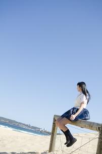 ビーチで柵に腰をかけている制服姿の女の子の素材 [FYI01077215]