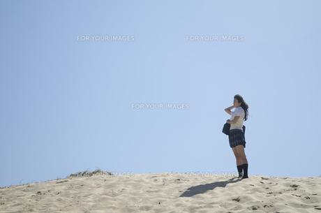 ビーチにたたずむ制服姿の女の子の素材 [FYI01077216]
